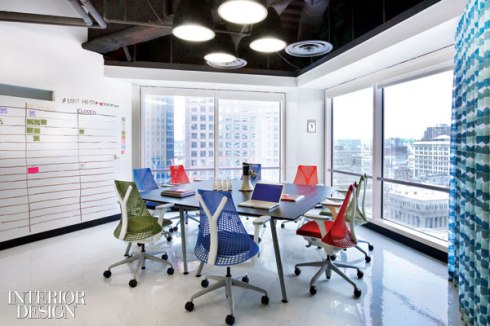 Yves Béhar chairs and white board panels furnish a meeting room.